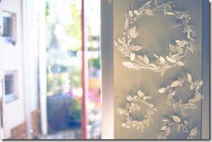 銀色の木の葉リースと開け放たれたドア