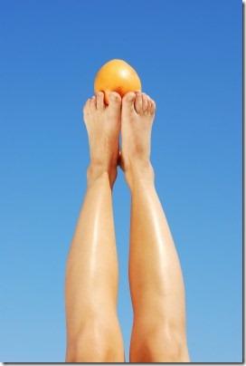 大空に伸びている素足でオレンジをキャッチ