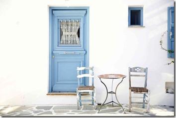 ブルーのドアと白い壁に椅子とテーブル